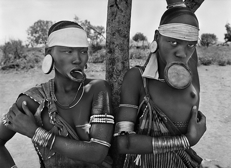 The Mursi and the Surma women are the last women in the world to wear lip plates.  Mursi village of Dargui in Mago National Park, in the Jinka Region. Ethiopia. 2007. © Sebastião Salgado / Amazonas images