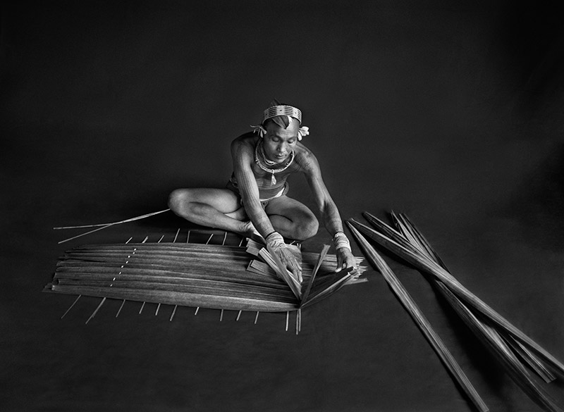 Teureum, sikeirei and leader of the Mentawai clan.  This shaman is preparing a filter for sago, with the leaves of this same sago tree. Siberut Island. West Sumatra. Indonesia. 2008. © Sebastião Salgado / Amazonas images